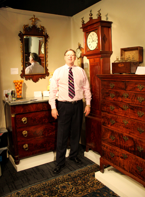 Canton, Mass., dealer Gary Sullivan with, right, a signed Boston tall clock by Aaron Willard in a Henry Willard case.