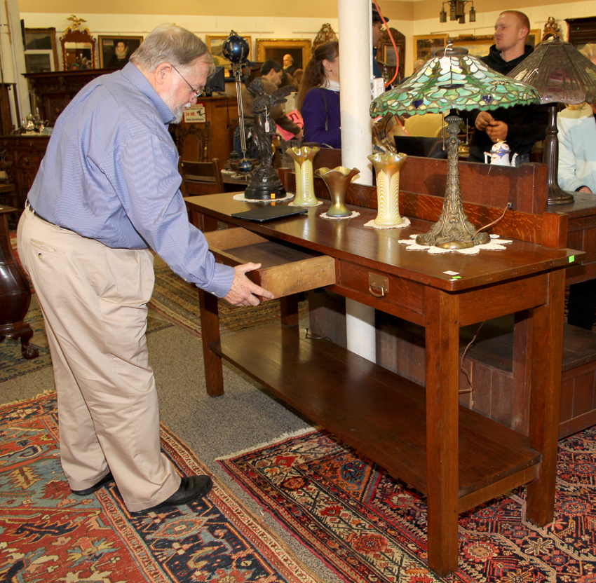 A prospective bidder checks out a Mission oak server with hammered-copper pulls, $ 3,300 ($ 500/800). Duffner & Kimberly leaded-glass lamp, right, in a Thistle pattern with thistle and fleur-de-lis decorated vase, $ 13,200 ($ 12/18,000). Flanking a Steuben aurene vase, $ 375, is a pair of iridescent, feather design art glass vases attributed to Quezal, $ 480.