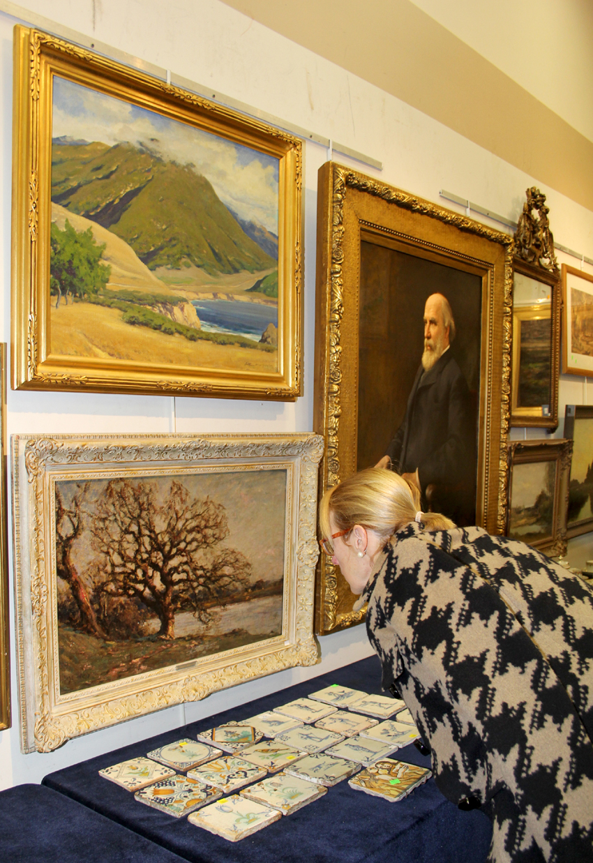 "Regional American landscapes performed well. Above left, ""Hills of Carmel Highlands  overlooking Mount Doud, Big Sur,"" a signed, oil on canvas by California artist Arthur Hill Gilbert (1894–1970), $ 25,200 ($ 6/10,000). Below, a prospective buyer inspects ""Flooded Arun"" by the Anglo French artist Jose Weiss (1859–1919), $ 660 ($ 800–$ 1,200). Right, from the Credit Suisse collection, oil portrait of James Jerome Hill, a Canadian-American railroad executive, by Adolfo Muller-Ury (1862–1947), circa 1902, $ 15,600 ($ 2/4,000). On the table, 19 polychrome decorated Delft tiles, $ 1,560 ($ 200/300)."