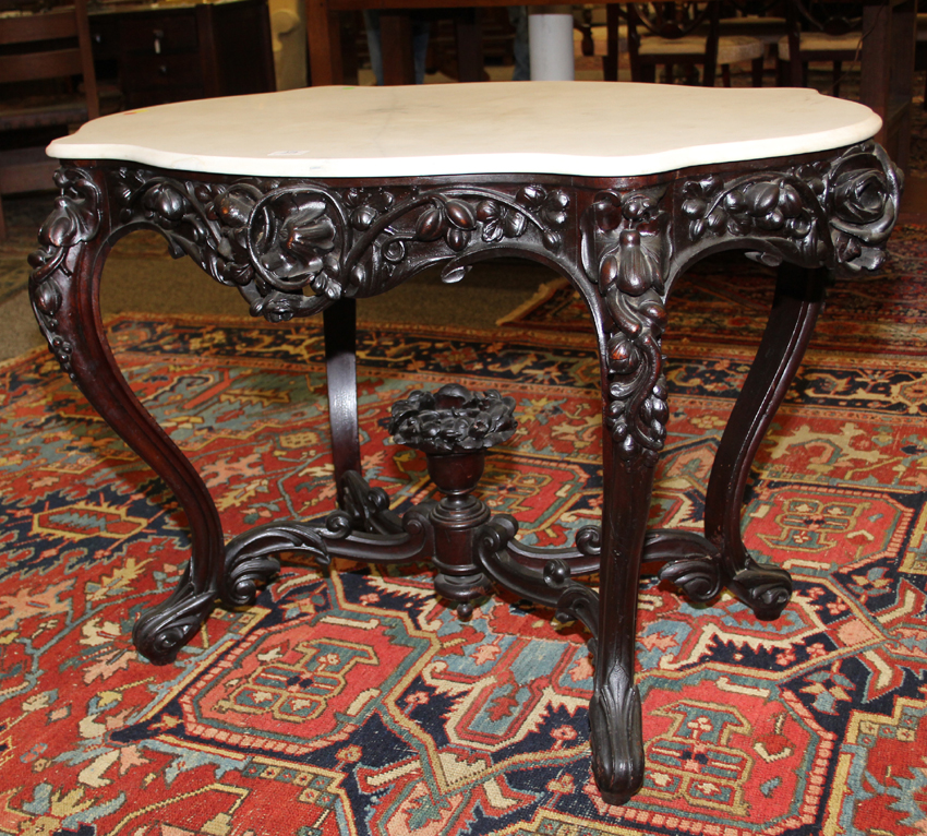 The sale included a single-owner collection of marble-topped Victorian tables. One of the best was this circa 1860, floral-carved rosewood example, $ 4,200<br>($ 3/5,000), in the manner of New York cabinetmaker John Henry Belter.