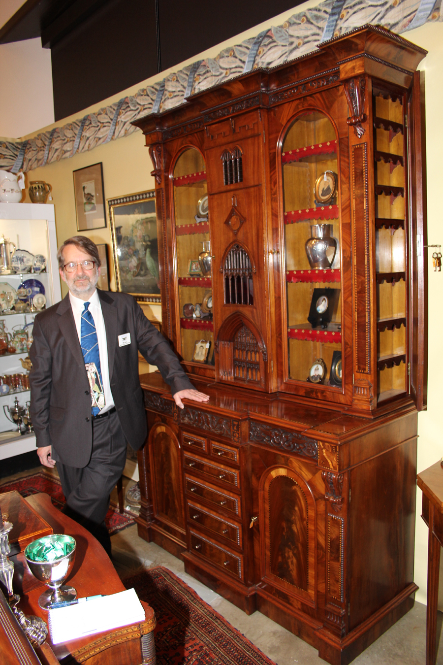 Bill Beck of Beck's Antiques, Fredericksburg, Va., with a spectacular desk-and-bookcase made for the Kendal and District Industrial Exhibition of 1872. The center door represents the central tower of the Kendal Parish Church in Kendal, Westmorland, U.K.