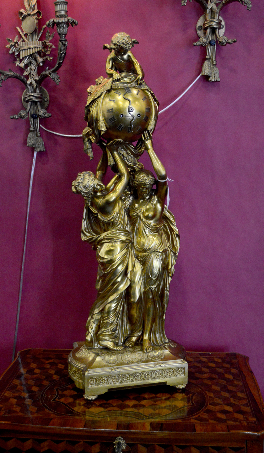 Antique Elements, Roslyn, N.Y., offered a French dore bronze Neoclassical clock, signed Graux-Marly Paris, 34½ inches tall.