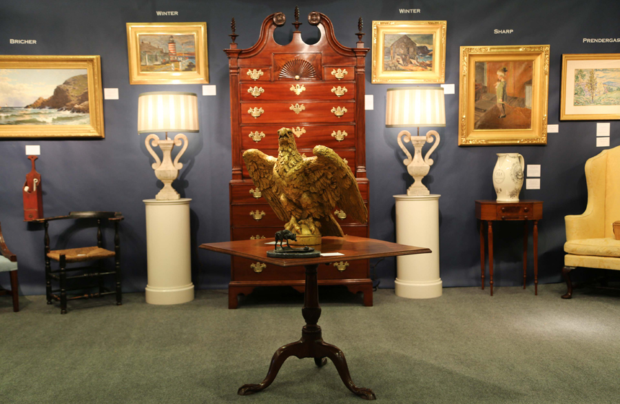 A Nineteenth Century American gilt carved eagle welcomed visitors to the booth by Roberto Freitas, Stonington, Conn., with a Nineteenth Century Chippendale chest on chest in the background among works by Andrew Wyeth, John Singer Sargent, Ernest Lawson and Alfred Thompson Bricher.
