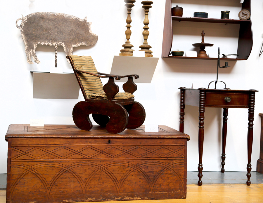 An early child's chair from Maine sits atop a New England blanket chest<br>in Doug Ramsay's booth, Hadley, Mass.