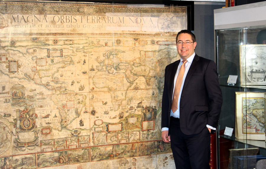 London dealer Daniel Crouch with a massive map by Portuguese artist Luis Teixeira, Magna Orbis Terrarum Nova Universalis, 1604, at his booth.