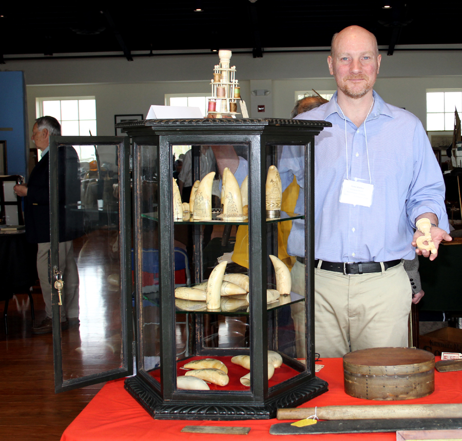 Sandwich, Mass., dealer Parke Madden holds a circa 1850 pincushion clamp made of sperm whale ivory. In his case are nearly two dozen scrimshaw teeth.