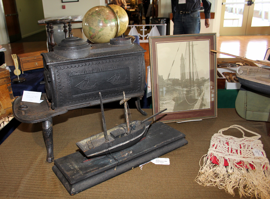 Charles Muenchinger of Central Falls, R.I., arrayed a #7 model ship's stove cast<br>by Tyson Furnace, Plymouth, Vt., 1839, with a photograph of the <i>Morningstar</i><br>on Lake Erie, a macramé bag and a pond model.