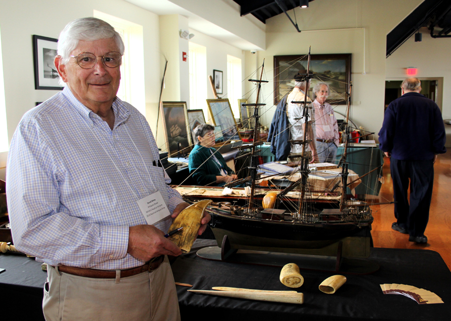 Dave White with a scrimshaw tooth engraved with figures of animals and ships. The North Yarmouth, Maine, dealer is also known for pond yachts,<br>dioramas and marine art.