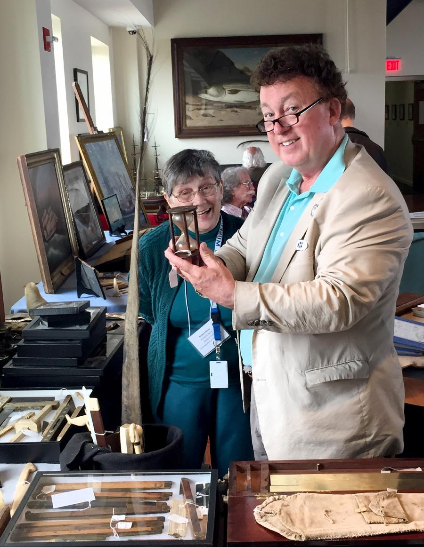 Barbara Moss of Westport, Mass., shows an hourglass to a customer.
