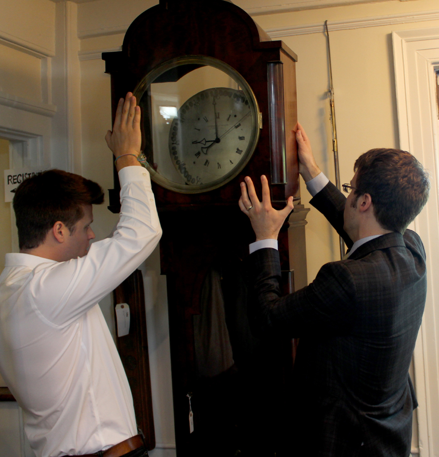 Butterscotch's Alexander Fonarow, left, helps the firm's Brendan Ryan place the hood atop the rare J.R. Brown & Sharpe wall clock prior to auction day's preview.