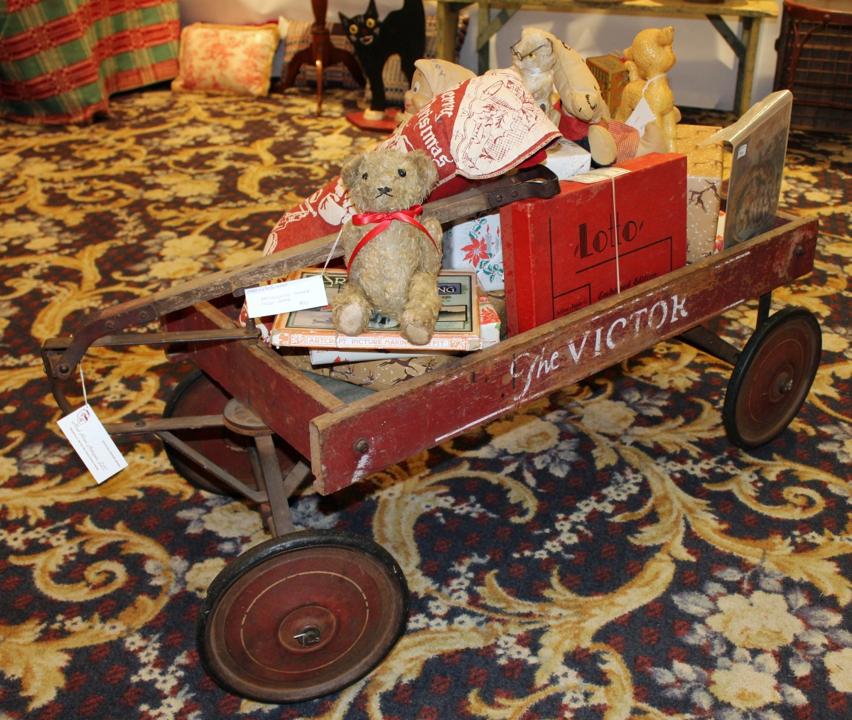 "Loaded WITH Bear — and more — at Mad River Antiques, North Granby, Conn., this 1920s toy wagon by ""The Victor"" was filled with many holiday goodies. Co-owner Lorraine German repurposes vintage items like this fishing creel to make a fetching holiday decoration."