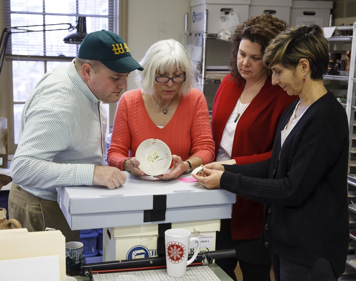 A white punch bowl is examined and discussed here in the archaeological laboratory of Commonwealth Heritage Group, Inc, West Chester, Penn., February 2016. —Robert Hunter photo