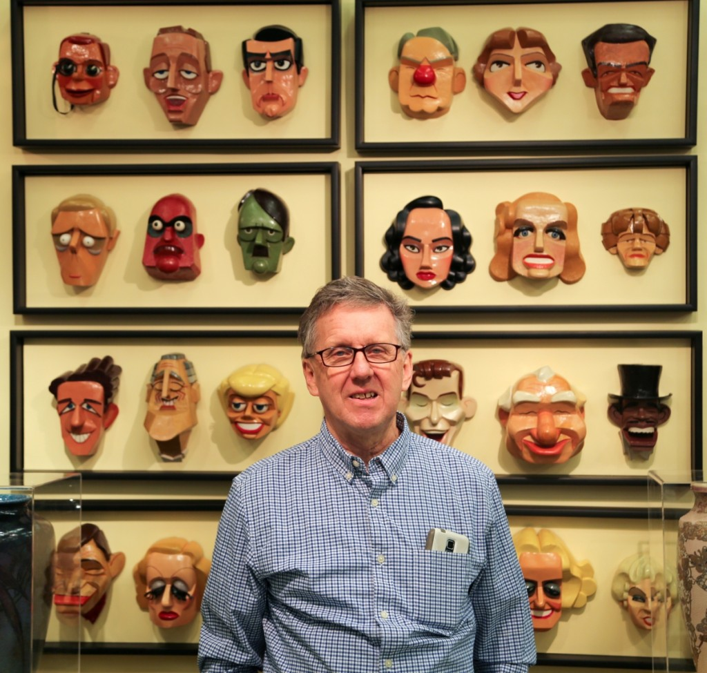 Paul Thien, Firehouse Antiques, Galena, Md., stands with his selection of masks from George Roether.