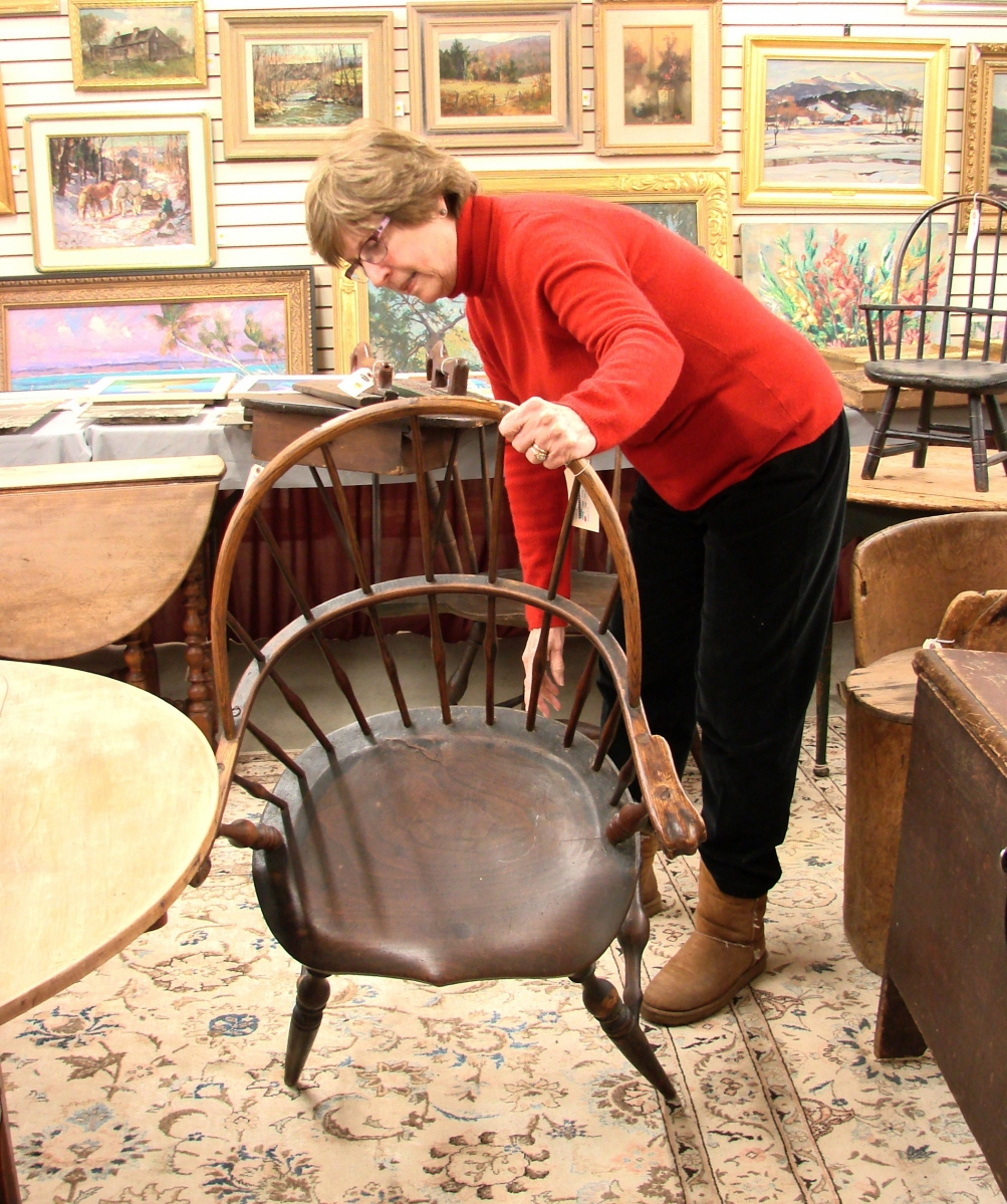 Gail Piatt, a Chichester, N.H., dealer, examines one of the Windsor chairs in the sale.