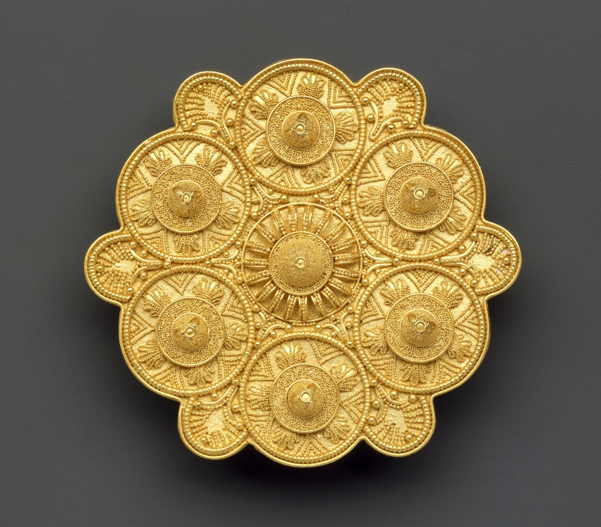 This circa 1858 lobed brooch by Alessandro Castellani (1823–1883) was modeled on a similar ancient Etruscan work that was part of the Campana collection, then in Italy. The jeweler had the opportunity to study and copy pieces before the archaeological artifacts were sold to the French in 1861. The Sixth Century BCE original ornament that inspired this brooch is in the Louvre.