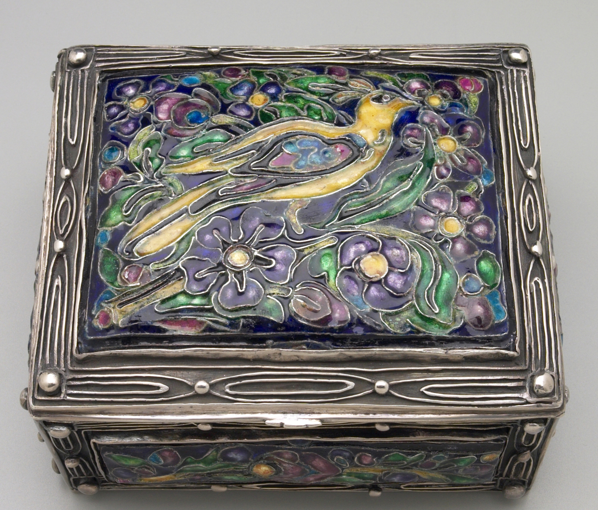"An Arts and Crafts BoxBox by Elizabeth Copeland, 1907–16. Sterling silver with colored enamels. Mrs Paul Moore Fund.Following the show ""The Arts and Crafts Movement in America, 1876-1916"" at Princeton University Art Museum in 1972, Yale curators focused on building collections that responded to this change in taste at the turn of the Twentieth Century. Shunning the machine and the factory system to return to handcraft practice of the preindustrial era, rich traditions are found in art pottery and metalsmithing. My first venture in building this aspect of the collection after becoming head curator in 1978 was to purchase this enameled silver box by Elizabeth Copeland from the firm of Lillian Nassau. Copeland worked in Boston. Her enamels evoke medieval prototypes and are consciously primitivistic. This stellar example of her work has a large enameled panel on the top and smaller ones on all four sides."