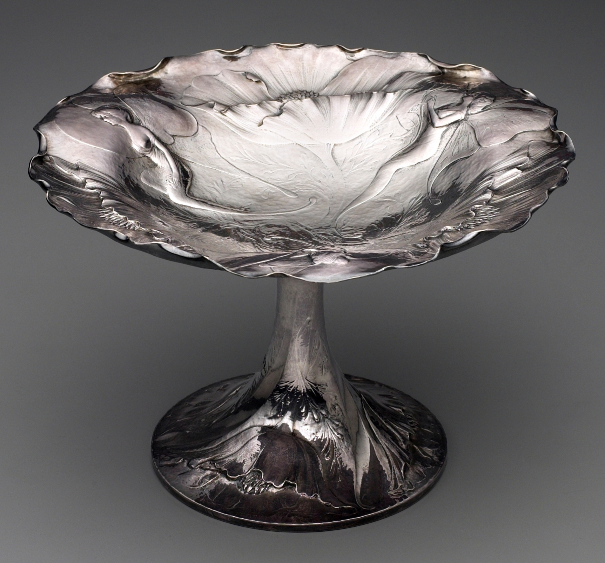A California CompoteCompote by Clemens Friedell, 1914. Sterling silver. Mabel Brady Garvan Collection, by exchange.In 2001, when scanning through a Skinner Discovery auction catalog, I was surprised to find this extraordinary compote with buxom lady fairies sitting amid California poppies by Clemens Friedell, recognized since the 1970s as an important Southern California silversmith from the Arts and Crafts Movement. Born in Louisiana, but trained as a silversmith in Vienna, Friedell was hired by the Gorham Manufacturing Company in Providence, R.I., in 1901 where he worked in the chasing room. He brought his formidable chasing skills to the company's deluxe Martelé line that featured repousséd and chased ornament in the Art Nouveau style. He later moved to California and established a shop in Pasadena by 1911. Because of his familiarity with Gorham designs, floral ornament and forms frequently characterize Friedell's silverware, but it is notably Pasadena's abundant flowers that inspired the design of this compote.