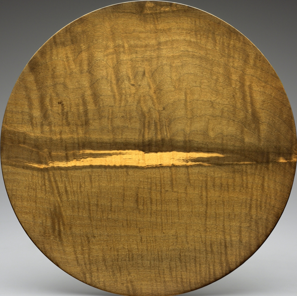 "The Wood Turner's ArtPlate by Bob Stocksdale, 1952 or 1953. English harewood. Mabel Brady Garvan Collection, by exchange, and a gift from Stephen S. Lash, BA,1962, in honor of Ruth and David Waterbury, BA, 1958.In addition to manufactured objects, we also collect contemporary handcrafted work. This plate by Bob Stocksdale represents a concerted effort in that regard since it was part of the exhibition ""Wood Turning in North America Since 1930"" that we organized with the Wood Turning Center (now the Center for Art in Wood) in Philadelphia. A goal of the show was to establish the canon in this medium. This plate by Bob Stocksdale has an important place in that canon. It is an early example of Stocksdale's ability to capitalize on the features of a special piece of wood, in this case English harewood with a spectacular streak of color variation through its center, creating an unusually painterly composition. Its additional importance is that it was shown in the pioneering Craftmen's Educational Council exhibition ""Designer-Craftsmen, U.S.A."" 1953. An endowment established by Ruth and David Waterbury enables us to acquire work in this field."