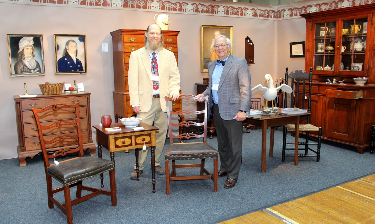 Kevin Tulimieri, left, and Arthur Liverant of Nathan Liverant and Son Antiques, Colchester, Conn. Objects of Connecticut interest included the pair of Chapin school ribbon back chairs and the pastel portraits of Lyme residents Lois Matson (1772–1825) and Deacon Nathaniel Matson (1765–1861) by New York City artist James Martin (active 1794–1820). On the Stonington, Conn., highboy is a Battle of Stonington creamware jug. Out of view is a 1772 Silas Merriman of New Haven tall case clock.