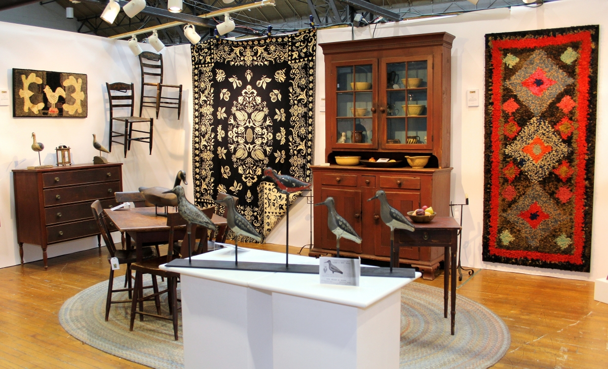 Arborfield Americana Antiques' colorful display mingled hooked rugs, a jacquard coverlet and, in the foreground, five plover shorebirds of painted tin by W.M. Read & Sons, Boston.
