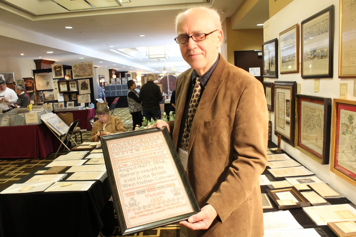Bill Subjack of Neverbird Antiques holds up one of the many sampler highlights, this one wrought by Agnes Mary Smith in 1837 referencing the end of slavery in the British West Indian colonies in 1834.