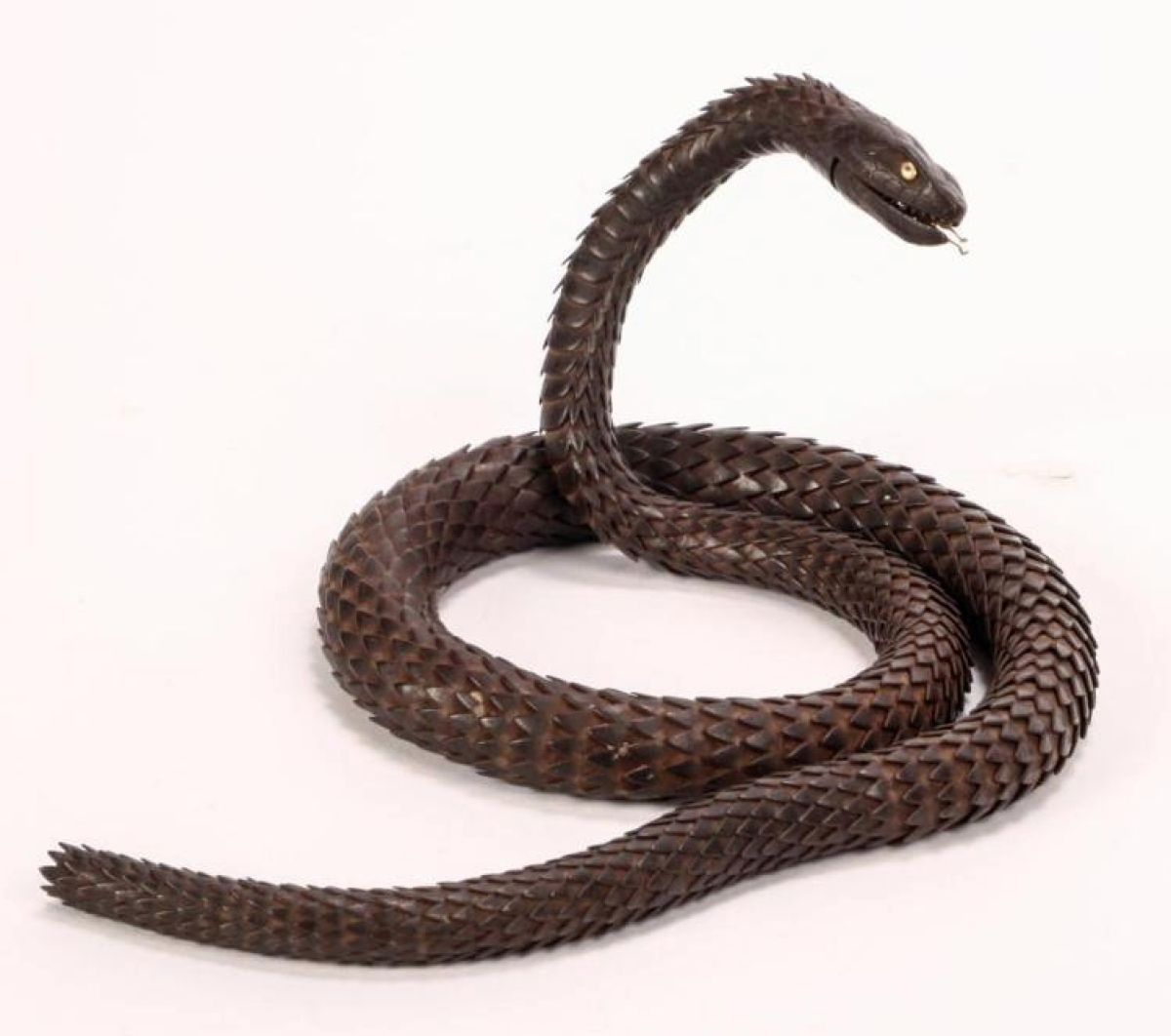 Constructed of numerous iron plates, this fully articulated Myochin School snake was made in Japan during the Meji period. The head is realistically carved with scales and a hinged jaw, a removable gilt tongue and gilt eyes. It finished at $26,400.