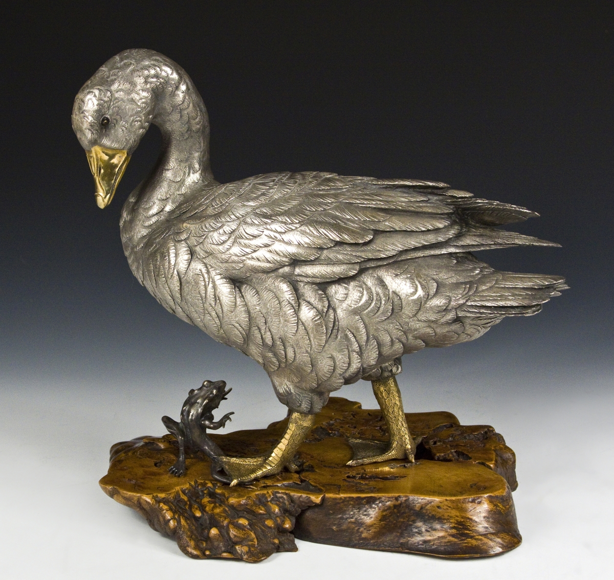 A silvered-bronze okimono of a goose, a small frog at its feet, gold, shakudo and shibuichi detailing, Seiji signature in oval cartouche under tail feathers. Provenance: Mr and Mrs Vincent Sardi, Vermont.