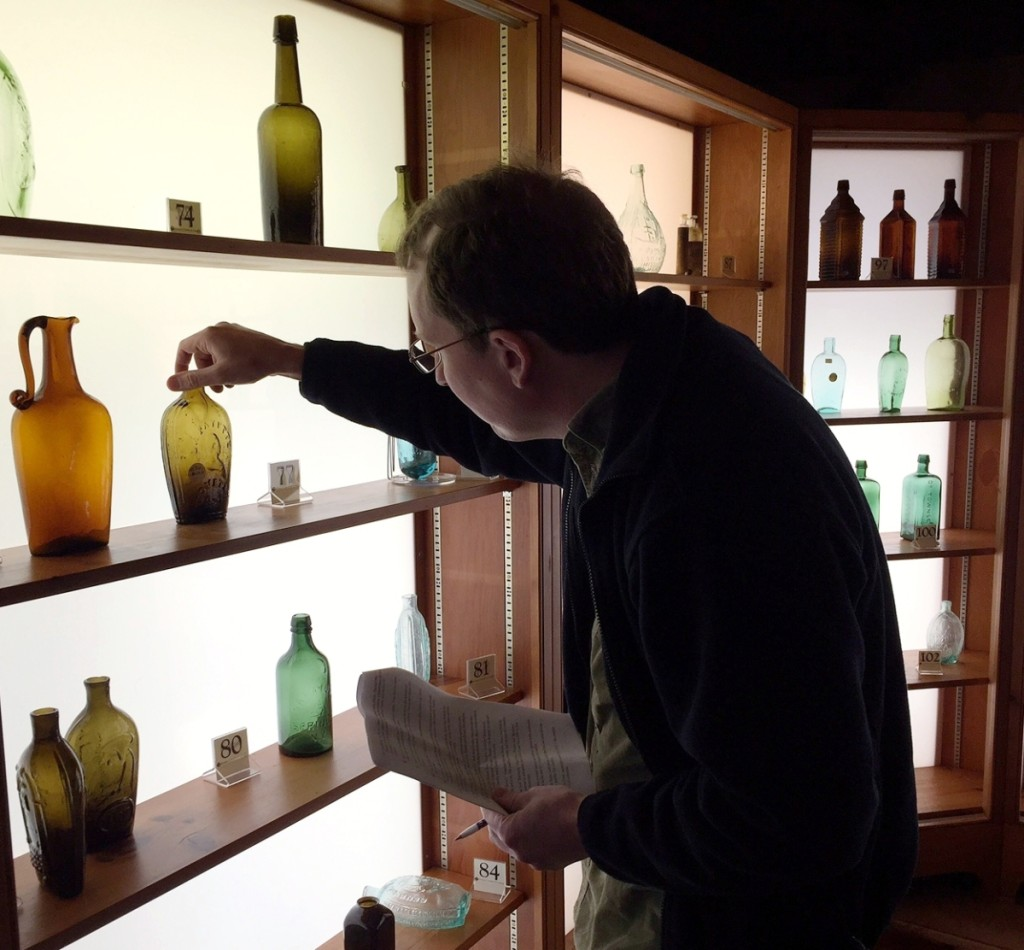 "A buyer checks out a ""Lafayette"" and bust/liberty cap pint portrait flask in olive amber, $1,112. Above, a ""Willington Glass Works"" quart whiskey bottle in medium olive amber, $293, and, below, a ""Saratoga / A / Spring Co. / N.Y."" pint mineral-water bottle in yellow green, $117. Bottom shelf, right, is a ""General Lafayette"" and bust with eagle and ""T.W.D."" portrait flask in aquamarine, $234."