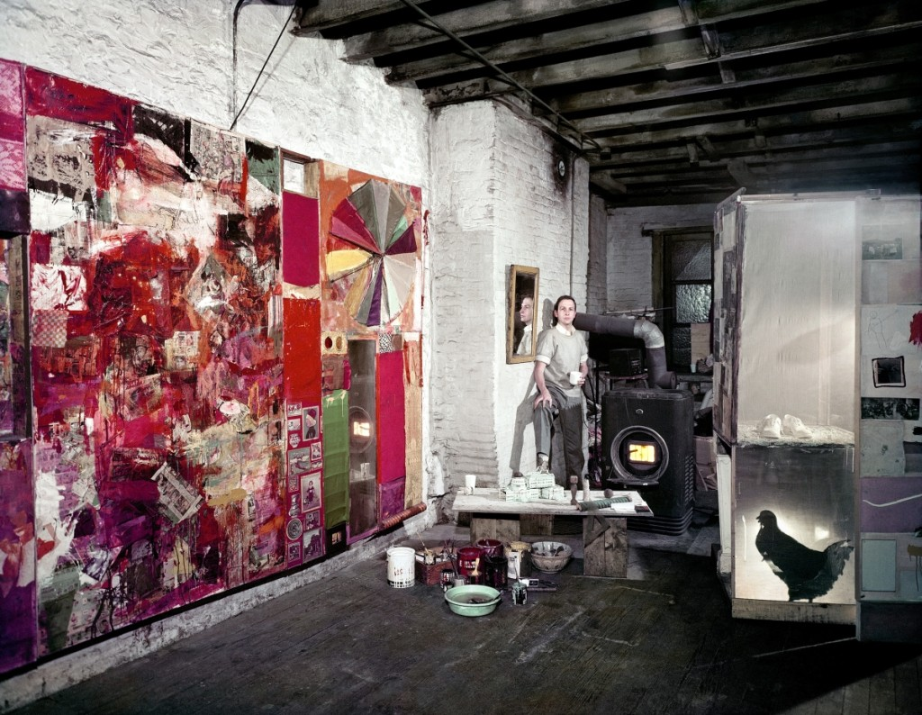 """Rauschenberg in his Pearl Street studio, New York, March 1958,"" photograph by Dan Budnik. Works shown from left are ""Charlene,"" 1954; untitled, circa 1954; and a partial rear view of the second state of ""Monogram,"" 1955–59, second state 1956–58. Courtesy Robert Rauschenberg Foundation Archives, New York. ©Dan Budnik, all rights reserved"