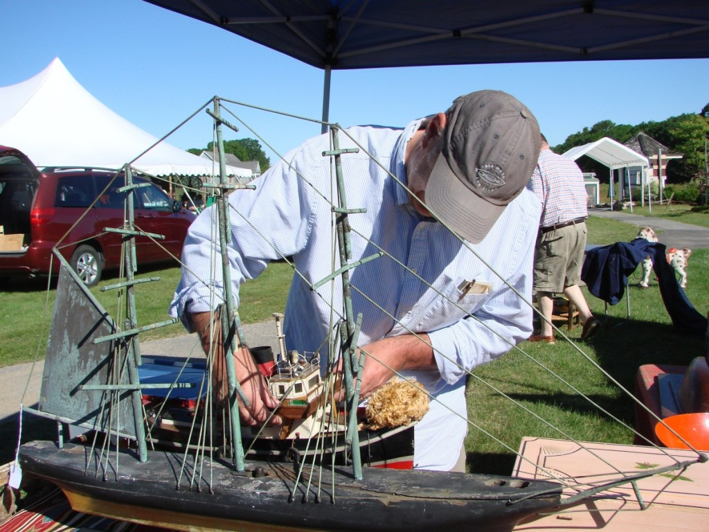 John Marshall, Florence, Mass., was putting the finishing touches on his display before the show opened. The ship weathervane was priced at $2,500, and the wooden tugboat was $950.