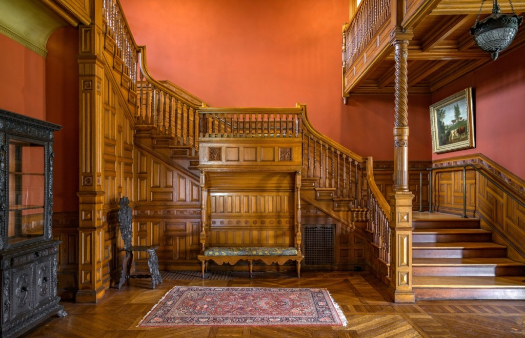 In the massive three-story hall, the carved woodwork and built-in benches are of oak. Paint analysis revealed the original red on the walls and green in the cove below the cornice.