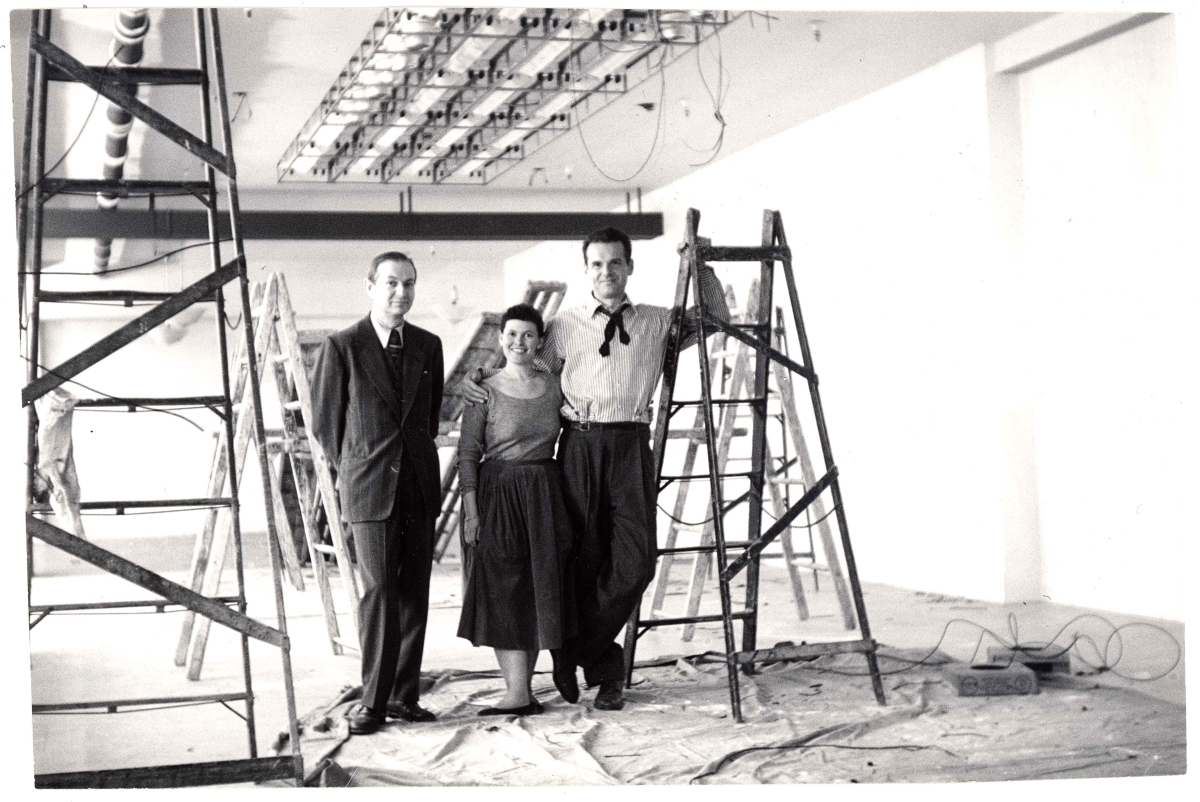 "Alexander Girard with Ray and Charles Eames while setting up the ""Good Design"" exhibition at the Merchandise Mart Chicago, 1953. Vitra Design Museum, Alexander Girard Estate"