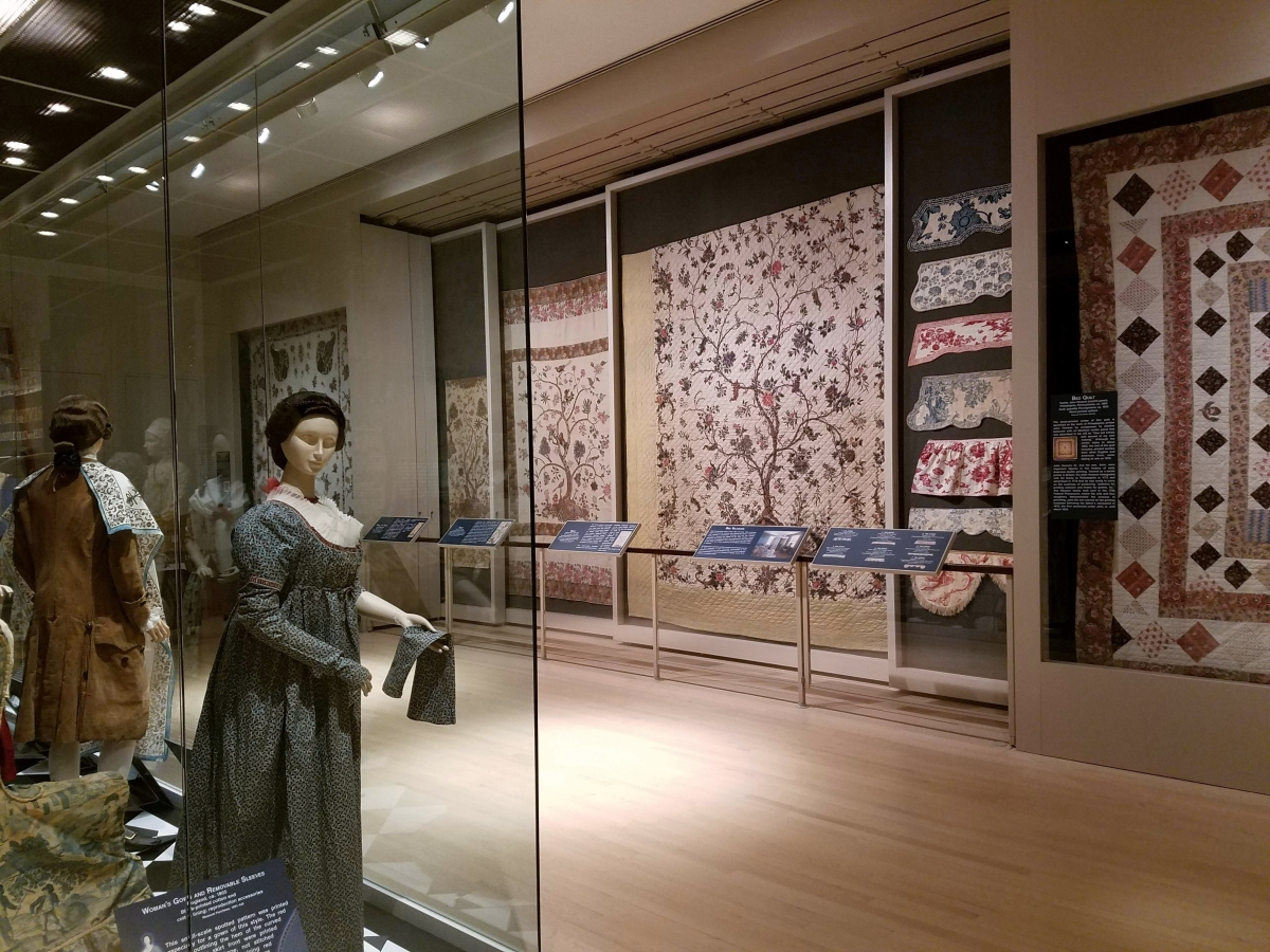 Printed textile fashions in the exhibition are displayed on mannequins in the central case, while larger bed coverings fill spaces along the wall. At center, an Indian chintz palampore, mordant painted and resist dyed, depicting an elaborate Tree of Life pattern; the cotton panel was made into a quilt in Europe 1770–90. Right, a series of printed canopy valances from sets of bed hangings.