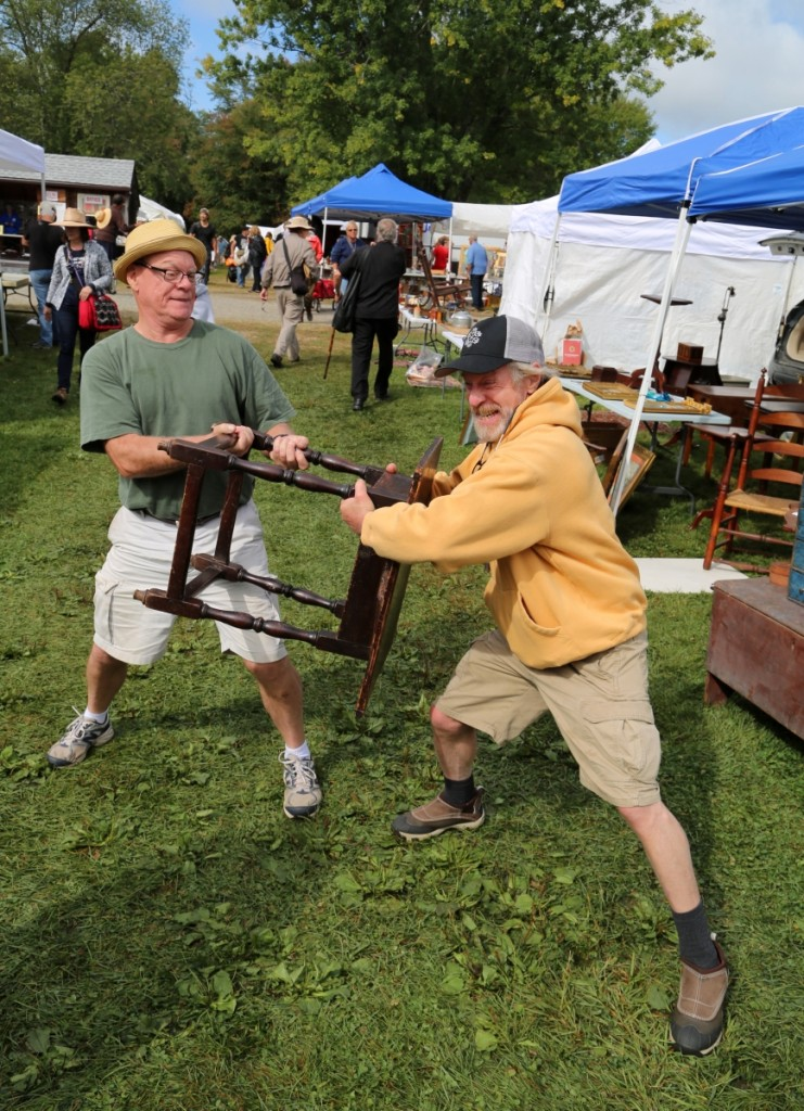 Derik Pulito and Don Heller battle it out over a Connecticut River Valley tavern table. Heller purchased the piece from Pulito, noting its special size and provenance to the Aaron brothers.         —May's Antique Market