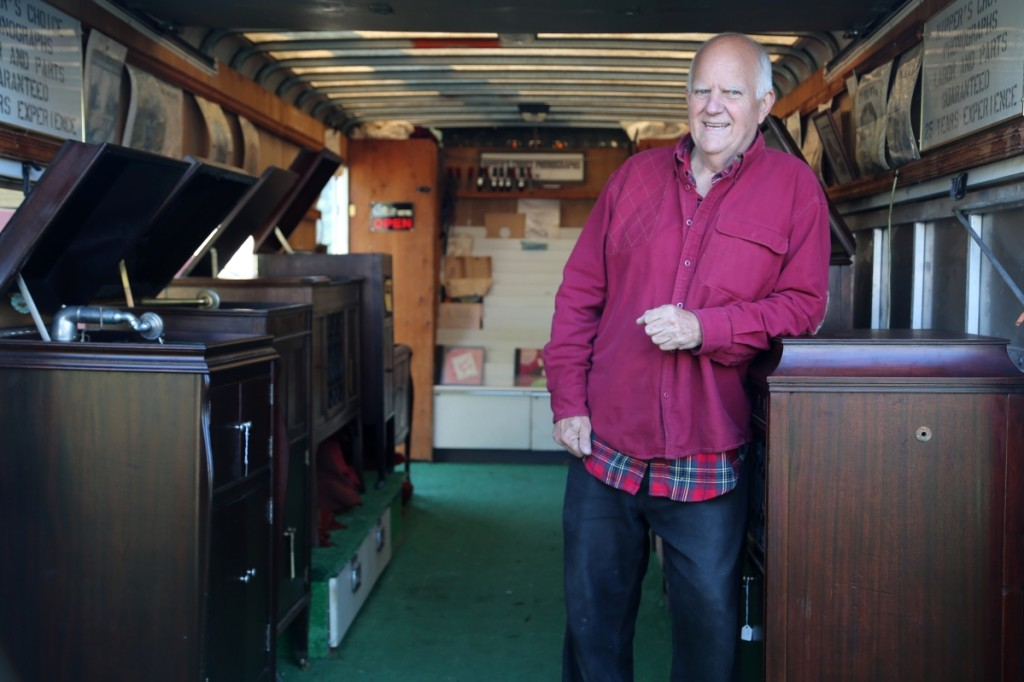 Ken Woodbury, Nipper's Choice, Keene, N.H., rests his elbow on a selection of phonographs that the dealer holds in his annex trailer.                       —J&J At Brimfield Auction Acres