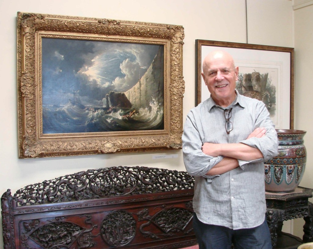 Carl Nordblom stands near the ornately carved Chinese settee.