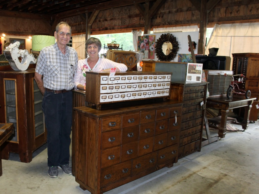 Ken Bailey and Tressa Mills stand proudly with some of the furniture pieces they have reclaimed as Finders Keepers, Holland, Mich. The hardware cubbies on top, for example, are late 1920s. Ken replaced the battered plywood top with rich dark oak, replaced the legs and back and gave them new life.                                                     —New England Motel