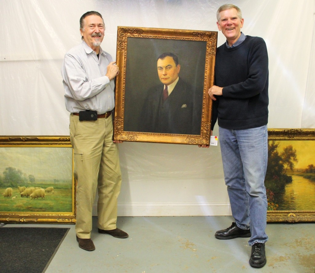 """Auctioneer Tom Schwenke, left, and Brock Jobe, Winterthur curator emeritus, hoist a portrait of C.K. Davis (1889–1968), past president of DuPont subsidiary Remington Arms and a mid-Twentieth Century collector of American antiques. The auction featured roughly 75 lots inherited by Davis's son William. Also among the Davis consignment, """"May Morning"""" by John Carleton Wiggins, $2,440, and, right, """"Evening Beaumont-le-Roger"""" by L. Aston Knight, $4,575."""