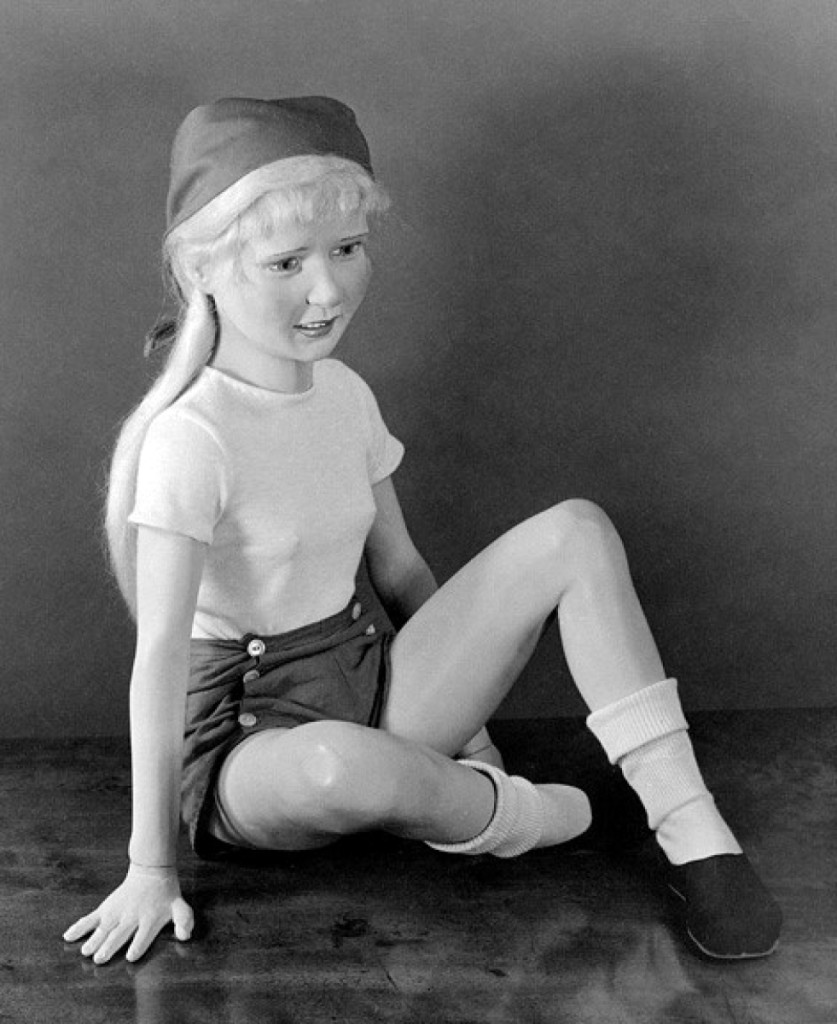 Morton Bartlett's untitled(Young Teenage Girl In Blonde Wig Sitting Cross Legged),circa 1950, silver gelatin print.
