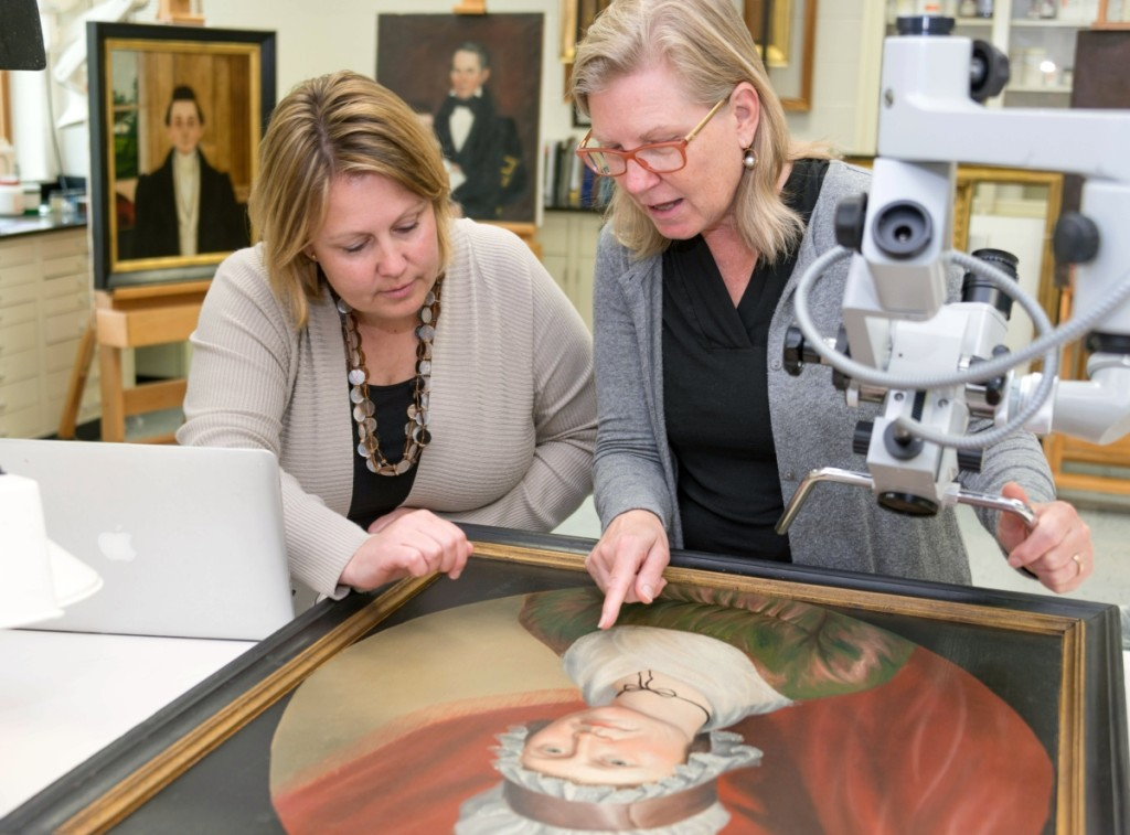 Laura Pass Barry, left, Colonial Williamsburg's Juli Grainger curator of paintings, drawings and sculpture, and Shelley Svoboda, senior conservator of paintings, examine the circa 1800 portrait of Matilda Morrow by Charles Peale Polk.                                                               —Jason Copes photo