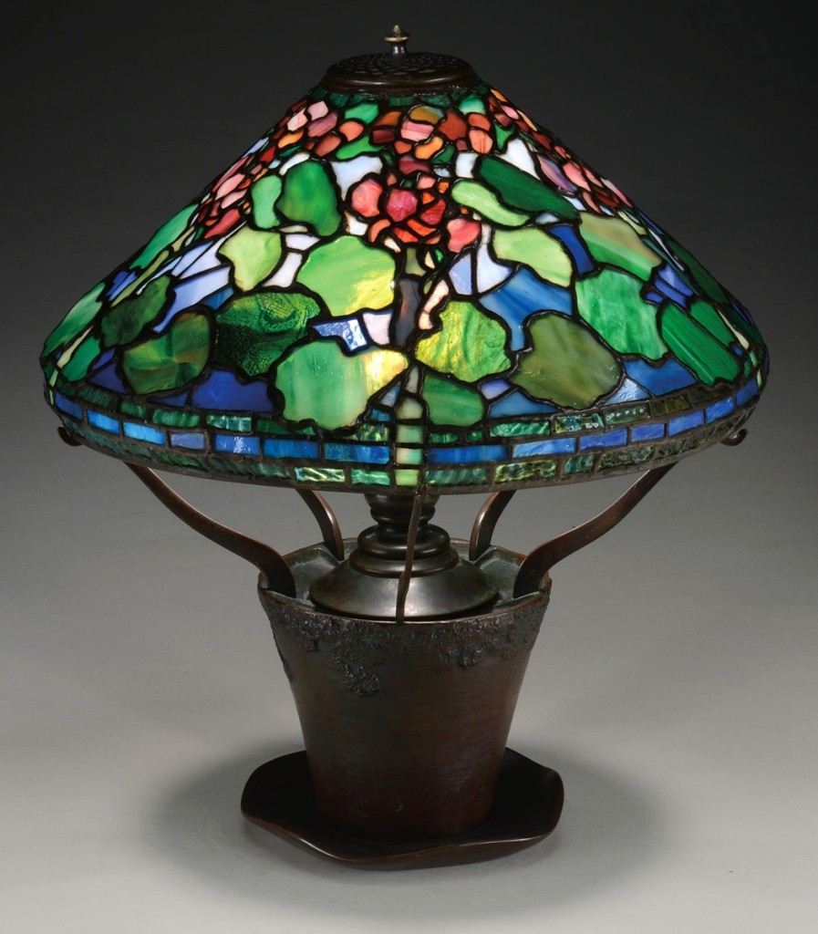 The signed Tiffany Studios Geranium pattern lamp, with a 16-inch shade, had red geraniums and mottled green leaves against a striated blue white background. It was one of three lamps that realized $84,700.