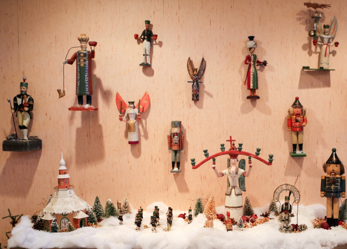 A wall of Erzgebirge figures. The mountainous area was relatively isolated through the Twentieth Century, when the reunification of Germany brought a huge upswing in tourism and interest in the region's Christmas tradition. Many of these figures were carved about a century ago as part of a cottage industry. Pre-1850s, the silver and tin mines brought some prosperity to the local residents, but the mines ran out at about the same time silver was discovered in the United States. Makers shifted to inexpensive wooden objects, like small toys and Christmas ornaments. These figures are a bit bigger and are about a foot tall. The angels are dressed in the distinctive manner of the Biedermeier period, and the men have on parade uniforms of the miner's organizations. Those parades continue today.