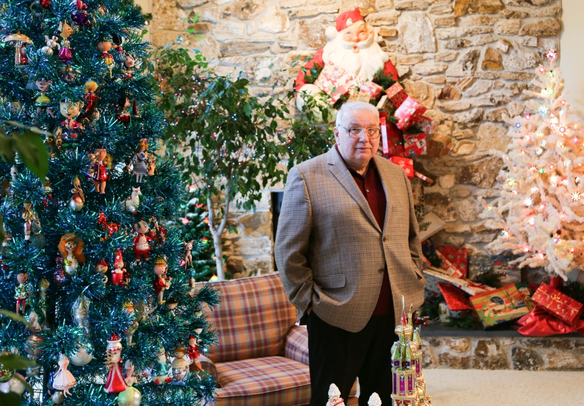Tony Annese has been collecting Christmas material since the 1980s. He stands beside his Christmas tree filled with Italian figural ornaments, a Santa Claus figure, rear, with gifts overflowing from his sack and cascading down to the fire hearth.