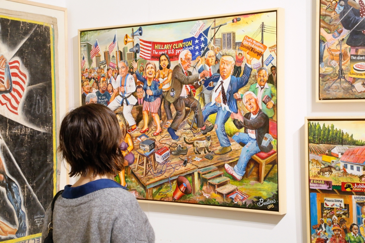 A viewer takes in a colorful and energetic work by Kenyan artist Joseph Bertiers in the booth of Ernie Wolfe Gallery, Los Angeles. Bertiers focuses on international politics and pop culture.