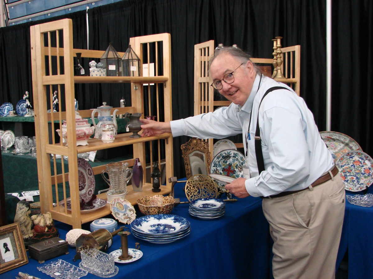 Roger Pheulpin, Gloucester, Mass., was putting the finishing touches on his booth before the show opened Saturday morning. He stocks a wide variety of ceramics and silver.