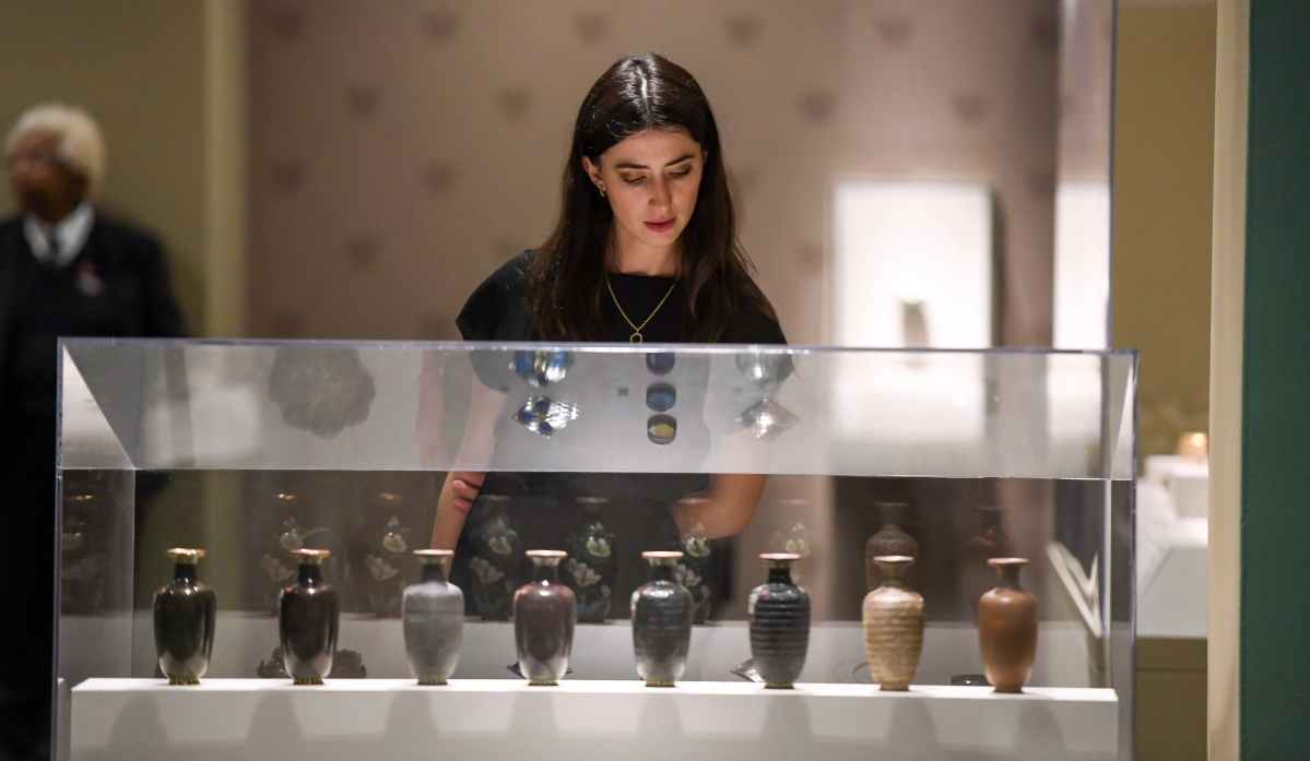 A visitor examines a series of vases illustrating the process of enameling used by Russian craftsmen. 							   —Maximillian Franz photo