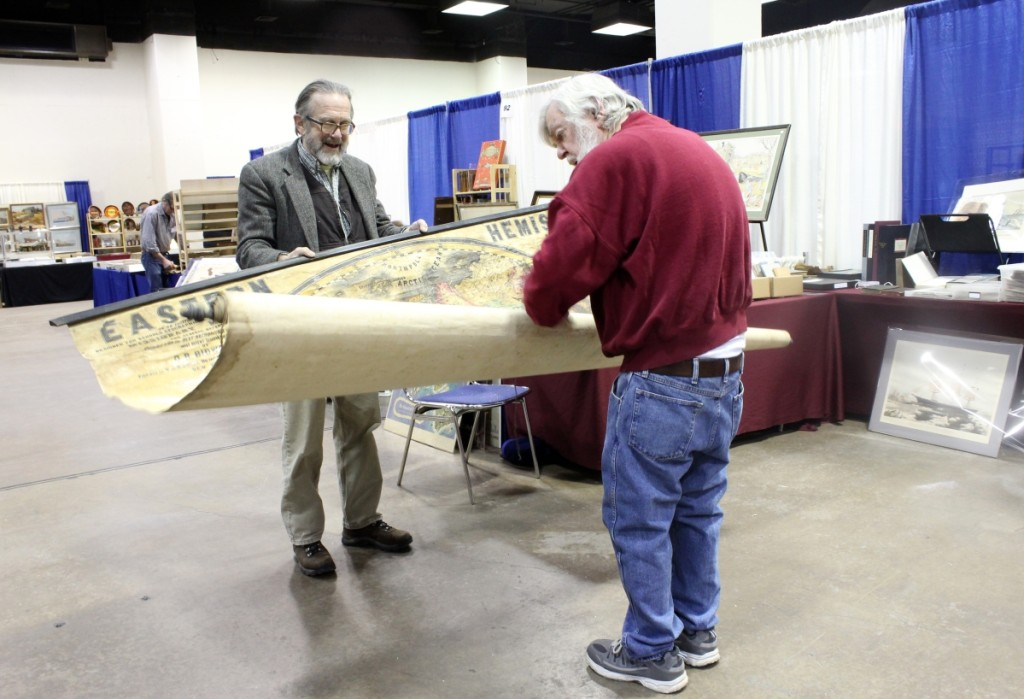 Greg Gibson, left, of Ten Pound Island Book Co., Gloucester, Mass., and dealer Bob Seymour unfurl a monumental map of the eastern hemisphere with a wealth of information on early expeditions, which Seymour eventually purchased and took home to study.