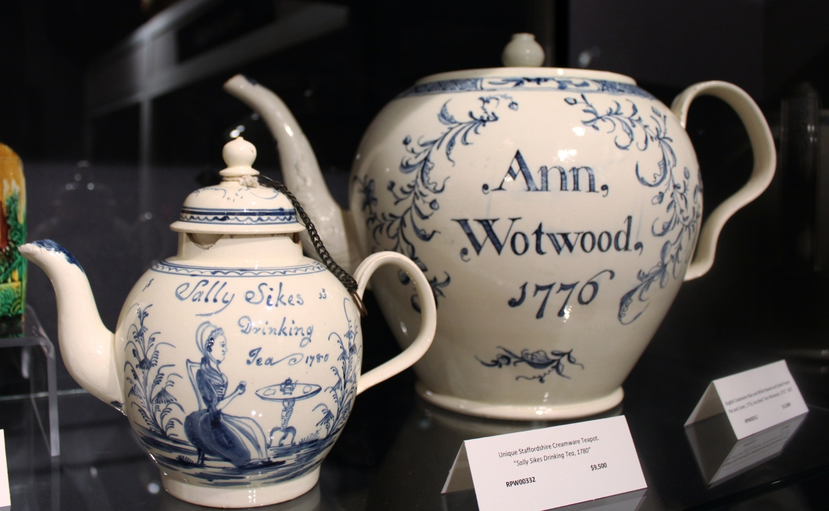 "Dealers who carefully research pieces that come into their inventory are often rewarded by interesting revelations. Such was the case when Robert Walker of Polka Dot Antiques, Waccabuc, N.Y., checked the bona fides of these two English creamware pieces — both unique. The small teapot at left is the only example he has seen naming its owner and proclaiming ""drinking tea."" Until it came into his hands it had been in the possession of the same family since 1780. Genealogical research on the larger teapot revealed that Ann Wotwood was actually Ann Watwood, a misspelling that did not spoil its appeal, what with the 1776 date."
