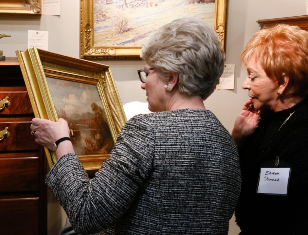 Chester County Historical Society president Elizabeth Laurent takes a closer look at a West Chester river landscape painting signed Geo. Cope, 1884.