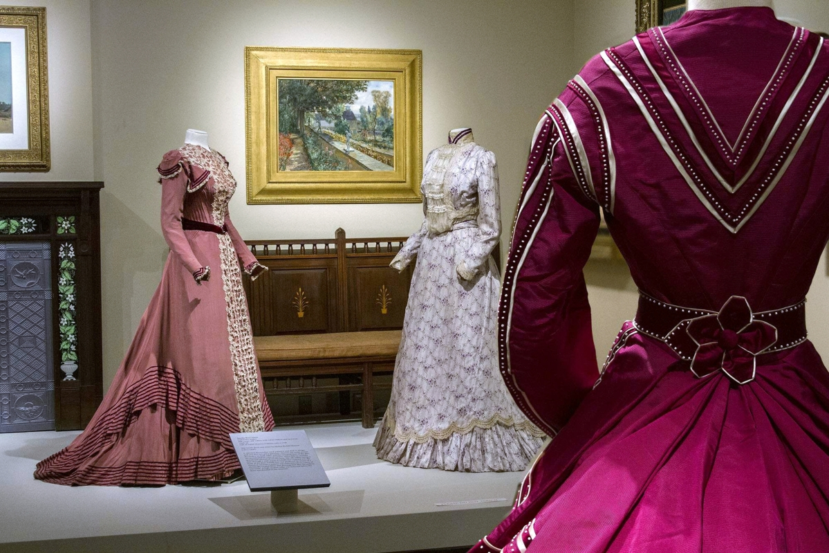 """Left, smoky-rose dress, 1898-99, and, right, violet and white dress, circa 1899, makers unknown. Foreground, back of raspberry dress with white beads by Marie and Josephine Virfolet, New York City, 1867. Rear, """"The Terrace Walls"""" by Will Hicok Low (1853–1932), 1901, oil on canvas."""